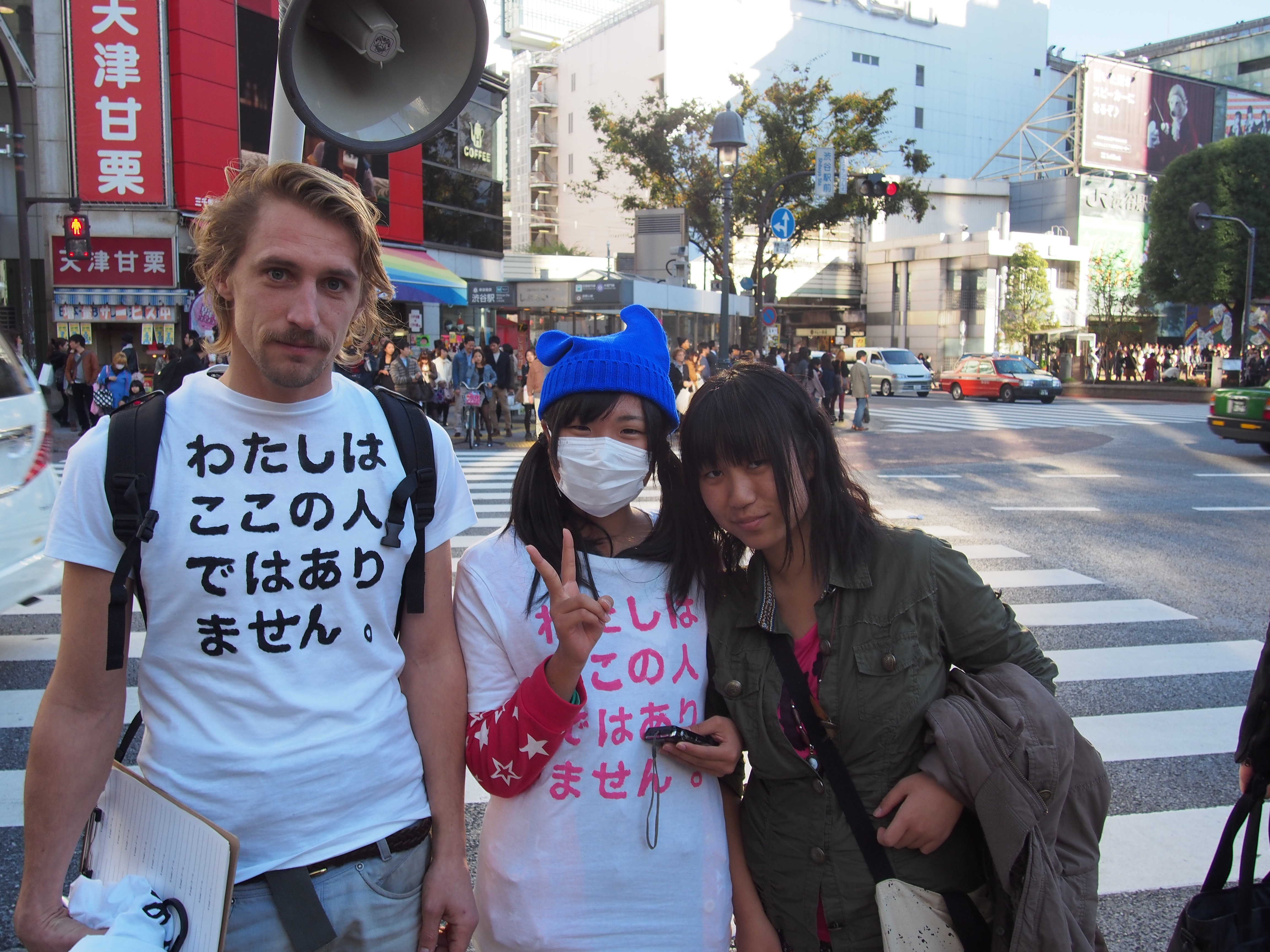 A Japanese lady was my spokesperson. From the megaphone strapped to my back here voice called: 'I am not from here, wear my T-shirts!' ある日本人女性が僕の広報係をつとめてくれた。私が背中に背負ったメガホンからは「わたしはここの人ではありません。私のTシャツを買ってください」という言葉が流れている。