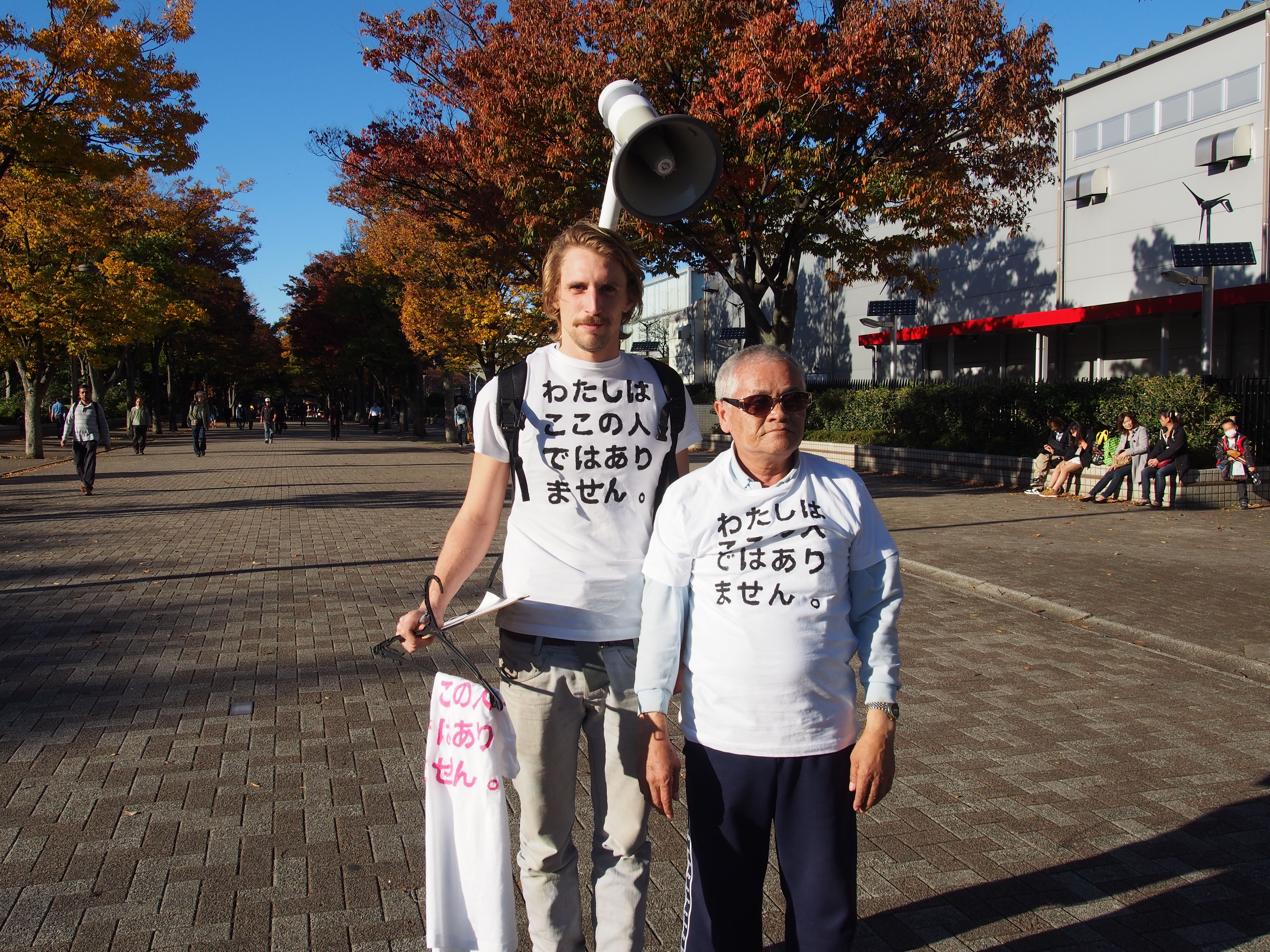 I took to the streets to sell my T-shirts. A white t-shirt with printed on it the text 'I am not from here'. 私は自分でつくったTシャツを売るために街に出た。白いTシャツには「わたしはここの人ではありません。」という言葉がプリントされている。